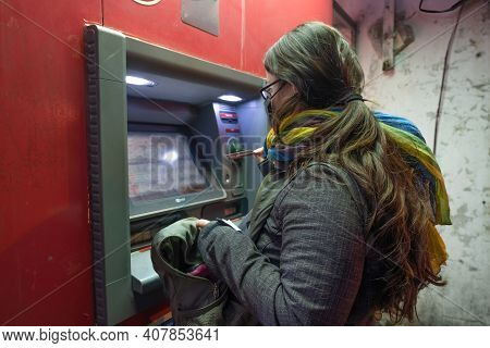 A Brunette Woman With Coat Withdraws Money From Atm In City In Winter Time