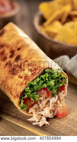 Closeup Of A Chicken Burrito With Lettuce And Tomato On A Wooden Cutting Board