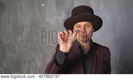 Portrait Of A Magician Biting A Coin, Standing On The Background. Inflation Concept. The Magician Bi