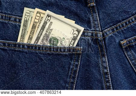 American Dollars In Jeans Pocket Background. Cash, Money Is In The Pocket Of Blue Jeans. Close-up