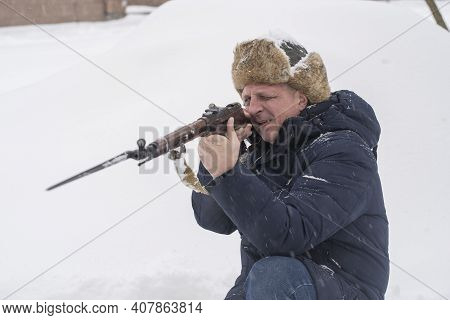 Man And Antique Mosin Rifle With A Bayonet In A Snowy Trench In Winter, Ukraine