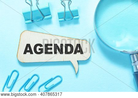 Agenda The Word Is Written On A Wooden Pop-up Box On A Blue Background, Stationery Lies Around.