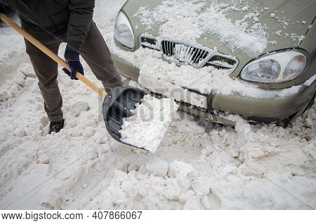 Man Digging Car Out Of The Snow. Man With A Snow Shovel Near The Snow Pile