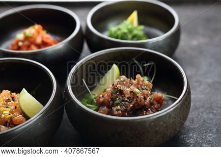 Tuna Tartare, Salmon Tartare On A Black Stony Background. A Composition Of Appetizers.