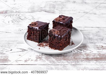 Chocolate Cake With Zucchini Topped With Ganache And Cut Into Portion Pieces On The White Table