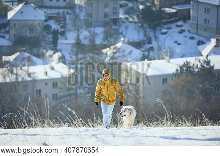 Happy Young Man With Dog In Winter. Pet Owner With His Labrador Retriever Walking In Snow Against Ci