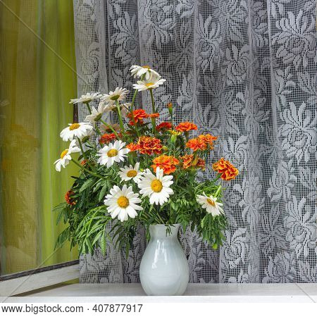 Simple Flowers In A White Glass Vase In An Old Window. Antique White Curtain In The Background. Swee