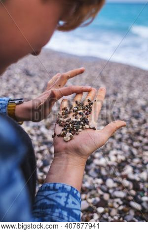 A Girl With Short Hair Sits On The Beach And Touches Pebbles, A Red-haired Girl Holds Small Pebbles