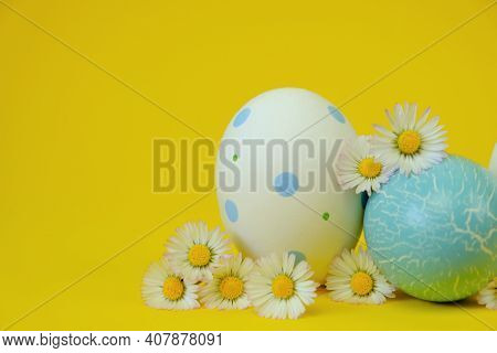 Easter Holiday. Easter White And Blue Eggs And Chamomile Flowers On A Yellow Background.spring Festi
