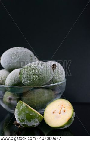 Iced Frozen Berries In Bowl. Many Whole Green Feijoa Berries With Cut One On Black Background. Prese