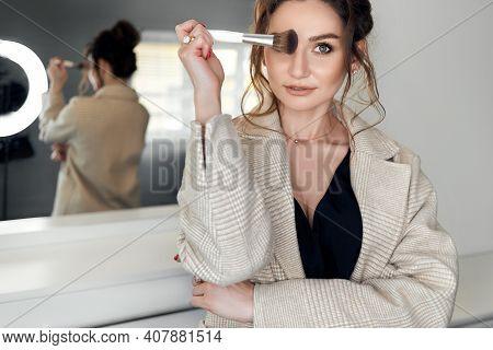 Beautiful Woman Make-up Artist Applies Makeup To Her Face. Makeup Artist With Makeup Brush In Hand.