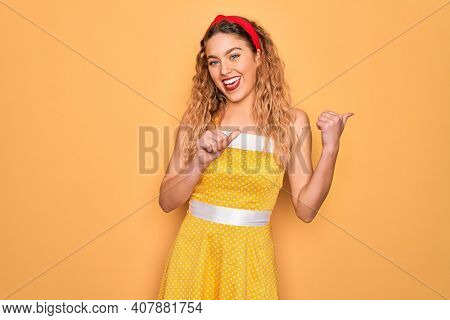 Beautiful blonde pin-up woman with blue eyes wearing diadem standing over yellow background Pointing to the back behind with hand and thumbs up, smiling confident