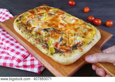 Hand Placing Delectable Fresh Baked Homemade Pesto Veggie Pizza On The Table