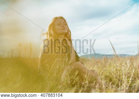 Against The Sky And Steppe Grass, A Woman With Her Hair Spread Over Her Shoulders And Her Neck Touch