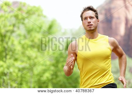 Sport - Runner. Man running with concentration, determination and strength towards goals and success in marathon. Fit male sport fitness model sprinting outdoors.