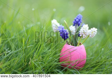 Easter Holiday Concept. Easter Egg And Flowers. Purple And White Muscari Flowers In Pink Decorative