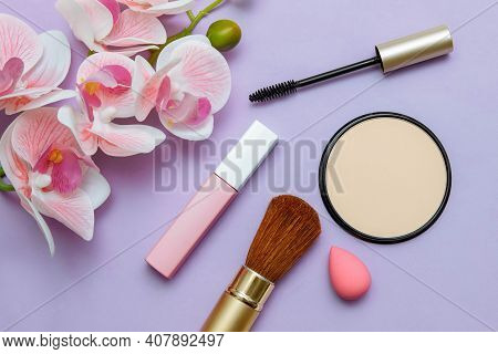 Decorative Cosmetics Mascara, Lipstick, Powder, Sponge And Bone On A Pink Background With Orchid Flo