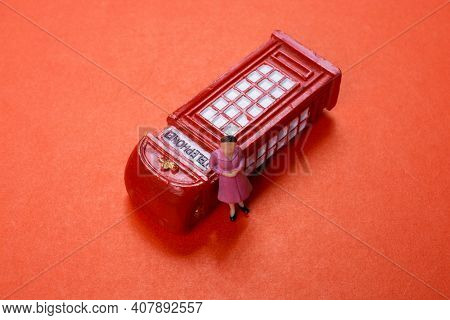 Classical British Style Red Phone Booth Model And Woman Figurine On Red
