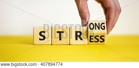 Strong Stress Symbol. Businessman Turns Wooden Cubes With Words 'strong Stress'. Beautiful Yellow Ta