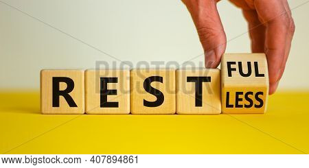 Restless Or Restful Symbol. Businessman Turns The Wooden Cube, Changes The Word 'restless' To 'restf