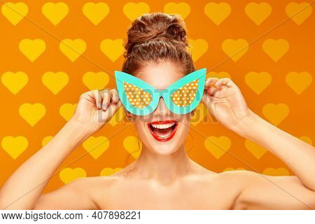 Pin-up style and beauty. Portrait of an exciting pretty woman posing in paper sunglasses in pin-up style on a yellow background. Makeup and cosmetics. Studio shot.