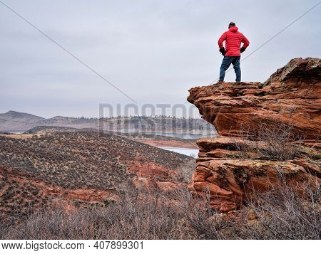 male hiker on a rocky cliff  at foothills of Rocky Mountains, Horsetooth Reservoir area - a popular recreational area in northern Colorado in fall or winter scenery with falling snow