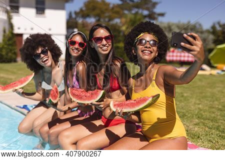 Diverse group of female friends taking selfie with watermelon sitting at the poolside. Hanging out and relaxing outdoors in summer.