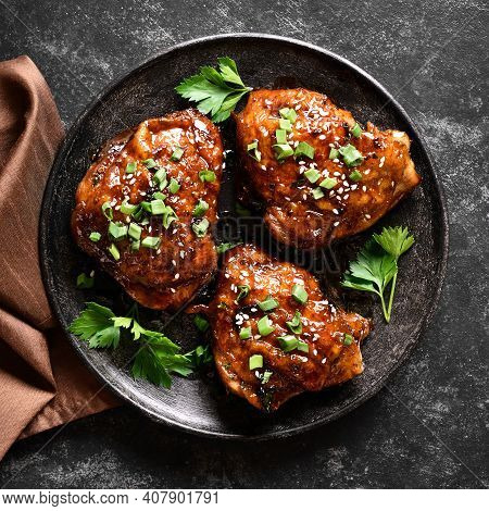 Sweet And Spicy Honey Grilled Chicken Thighs On Plate Over Dark Stone Background. Tasty Food In Asia