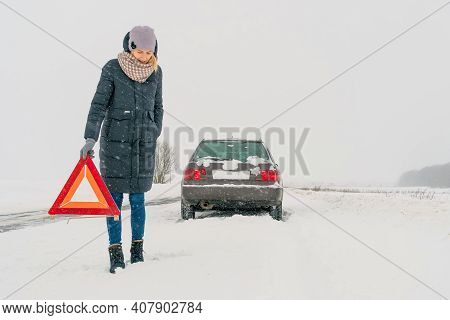 Young Girl In A Jacket, Hat, Scarf, Shoes Puts A Warning Road Sign Triangle On A Snow-covered Road A