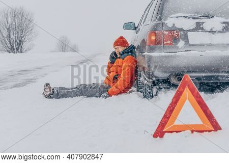 Desperate Young Man In An Orange Jacket Sits Near A Car And Talks On The Phone On A Snowy Road.he Is