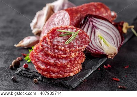 Traditional Smoked Salami Sausage With Spices.salami Sausage Slices On A Black Chopping Board. Dark