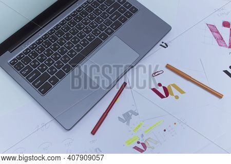 Creative Workplace Of A Graphic Designer. Development Of A Logo For The Company. Drawings And Sketch