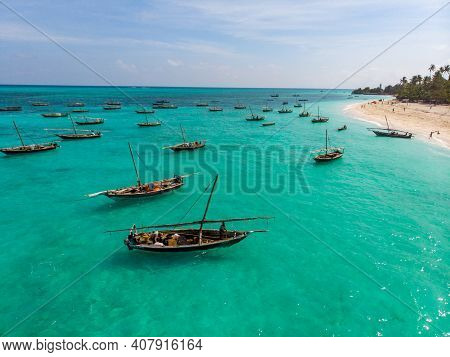 Traditional African Wooden Dhow Boats On Clean Turquoise Water Near The Coast Of Zanzibar At Nungwi