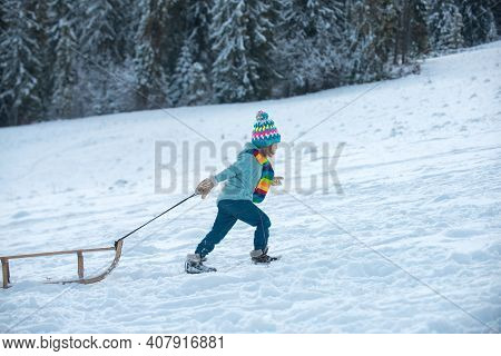 Winter Children Fun With Sled. Winter Outdoors Games. Happy Christmas Family Vacation Concept. Child
