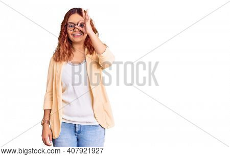Young latin woman wearing business clothes doing ok gesture with hand smiling, eye looking through fingers with happy face.