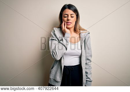 Young beautiful brunette sportswoman wearing sportswoman training over white background touching mouth with hand with painful expression because of toothache or dental illness on teeth. Dentist