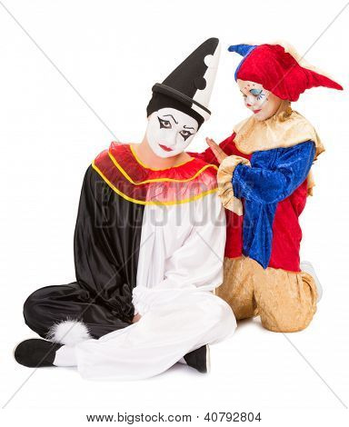 Sad pierrot getting consolation by a little girl clown