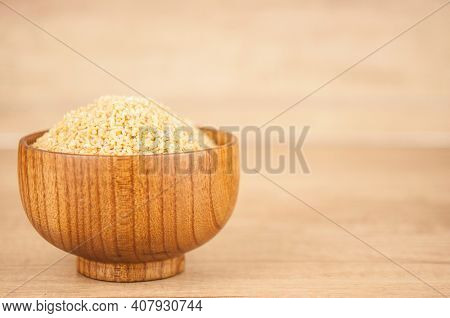 wheat groats in a wooden bowl on a wooden table background