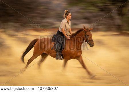 Slow Pan Of Blonde Riding Through Woods