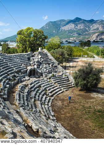 Tourist walking along ruins of Theatre in Letoon Ancient City in village Kumluova, Turkey. Sunny day, Greek culture ancient amphitheater architecture vertical photo
