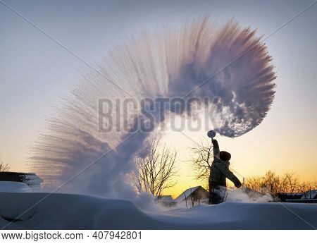 The Guy Splashes Boiled Water From A Thermos Over His Head Against The Backdrop Of A Sunset In Frost
