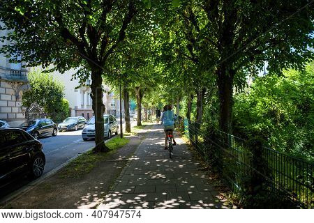 Strasbourg, France - July 29, 2017: Rear View Of Single Woman Cycling On The French Trottoir Under B