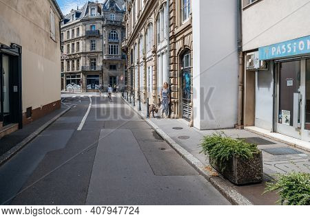 Strasbourg, France - July 29, 2017: Beautiful French Woman Walking Bulldog On The Almost Empty Stree