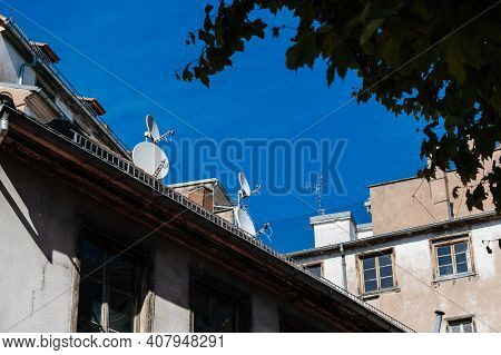 French Rooftops With Traditional Windows On Multiple Satellite Dishes On The Left Rooftop - Clear Bl