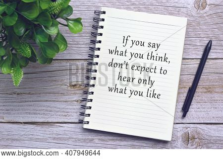 Motivational And Inspirational Quote On Notebook With Pen And Plant On Wooden Desk - If You Say What