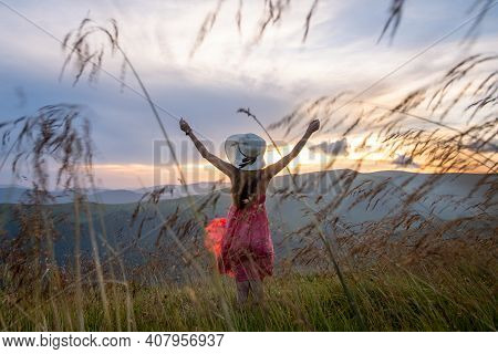 Young Woman In Red Dress Standing On Grassy Field On A Windy Evening In Autumn Mountains Enjoying Vi