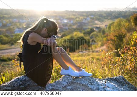 Young Depressed Woman In Black Short Summer Dress Sitting On A Rock Thinking Outdoors At Sunset. Fas