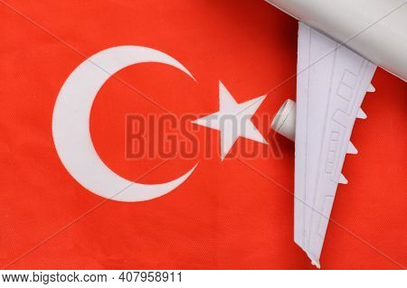 Travel Concept. Passenger Plane Wing Against The Background Of Turkish Flag