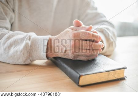 Senior Man Praying, Reading  An Old Bible In His Hands.hands Folded In Prayer On A Holy Bible In Chu