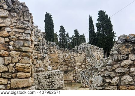 Antique Ruins - The Remains Of Stone Walls Against The Background Of A Cypress Grove